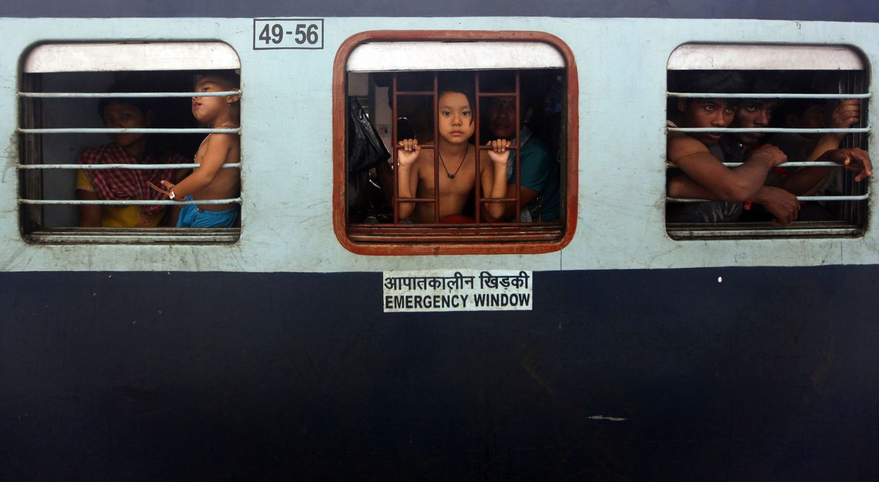 People from India's northeastern states sit inside a train bound for the Assam state at the railway station in Kolkata August 18, 2012. Indian Prime Minister Manmohan Singh assured migrants from the northeast that they were safe as thousands fled Mumbai, Bangalore and other cities on Friday, fearing a backlash from violence against Muslims in Assam. REUTERS/Rupak De Chowdhuri (INDIA - Tags: TRANSPORT CIVIL UNREST SOCIETY TPX IMAGES OF THE DAY) TEMPLATE OUT