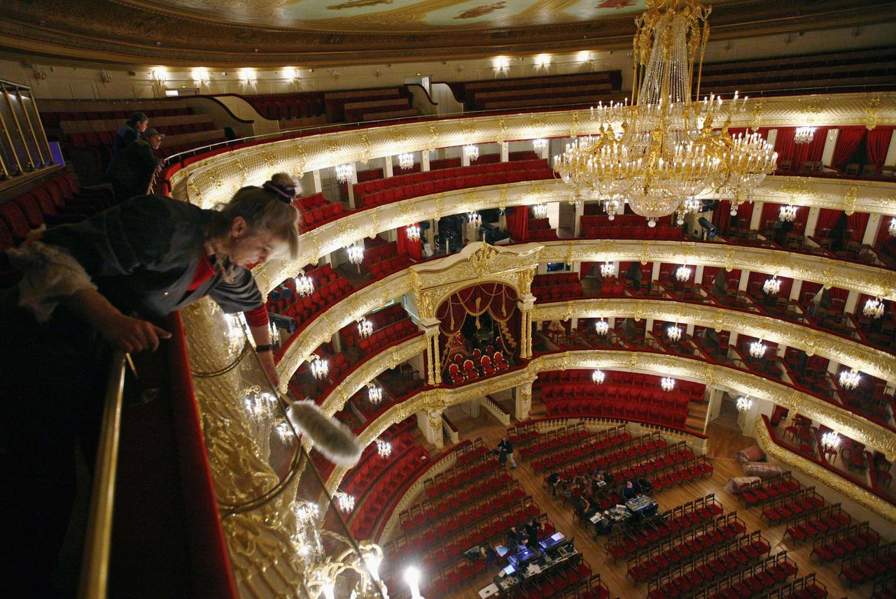 A worker cleans the newly refurbished main hall of Moscow's Bolshoi theatre October 24, 2011. Moscow's most famous theatre is set to reopen with a gala performance on Friday after six years of closure for renovation. REUTERS/Anton Golubev (RUSSIA - Tags: SOCIETY)