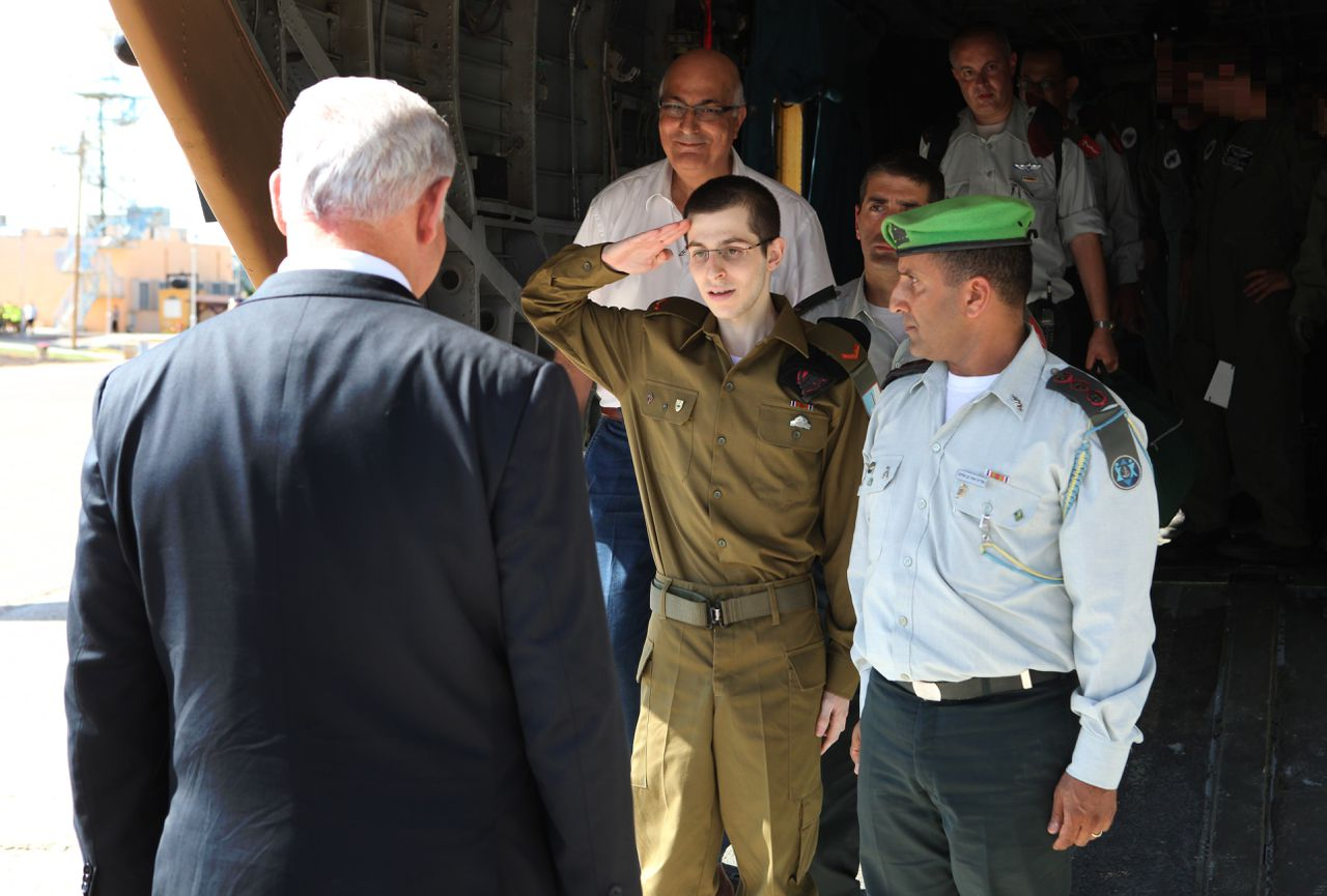 In this photo released by the Israeli Government Press Office, released Israeli soldier Gilad Schalit, center, salutes as he is welcomed by Israeli Prime Minister Benjamin Netanyahu, left, at the Tel Nof Air base in southern Israel, Tuesday, Oct. 18, 2011. Looking thin, weary and dazed, the Israeli soldier returned home Tuesday from more than five years of captivity in the Gaza Strip in exchange for hundreds of Palestinian prisoners whose joyful families greeted them with massive celebrations. (AP Photo/ GPO, HO) ISRAEL OUT