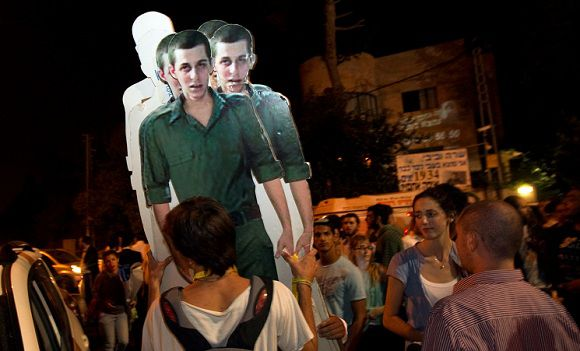 Caption: Israeli activists carry cardboard cut-outs of captured Israeli soldier Gilad Shalit outside the residence of Israel's Prime Minister Benjamin Netanyahu in Jerusalem October 12, 2011. Israel and Gaza's Hamas Islamist rulers agreed on Tuesday to swap more than 1,000 Palestinian prisoners for Shalit, resolving one of the most emotive and intractable issues between them. REUTERS/Ronen Zvulun (JERUSALEM - Tags: POLITICS TPX IMAGES OF THE DAY)