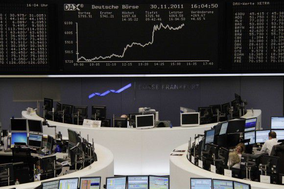Traders are pictured at their desks in front of the DAX board at the Frankfurt stock exchange November 30, 2011. REUTERS/Remote/Amanda Andersen (GERMANY - Tags: BUSINESS)