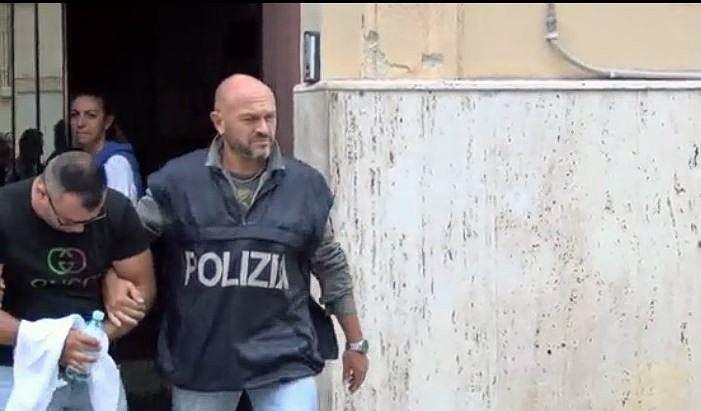 Een van de gearresteerden wordt overgedragen door de politie in Palermo.