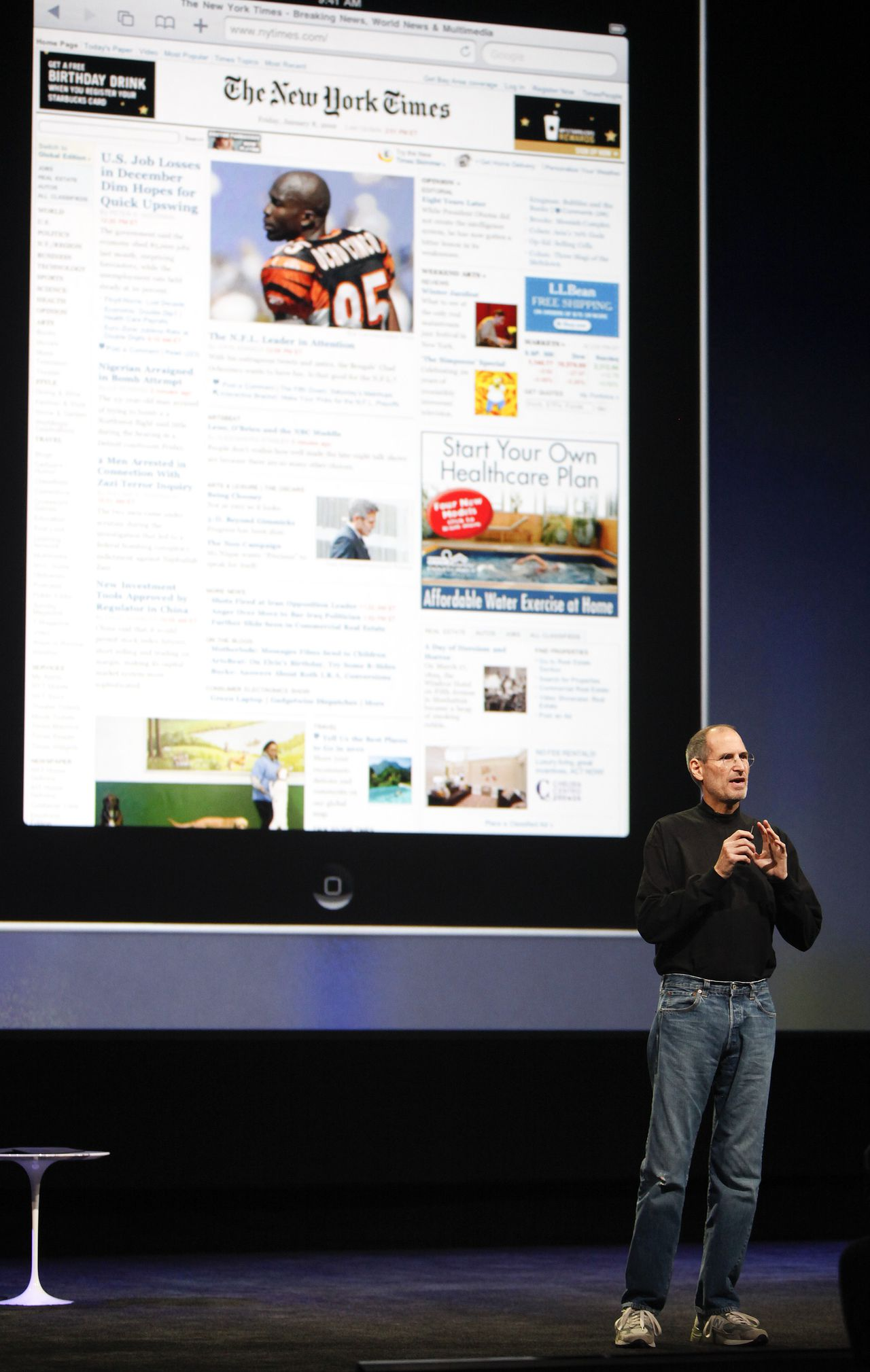 Steve Jobs van computerbedrijf Apple bij de lancering van de iPad computer in januari 2010. Foto Bloomberg Steve Jobs, chief executive officer of Apple Inc., speaks in front of an image of an Apple iPad tablet during its debut at the Yerba Buena Center for the Arts Theater in San Francisco, California, U.S., on Wednesday, Jan. 27, 2010. Apple Inc., trying to expand beyond the Macintosh, iPod and iPhone, introduced the iPad, a tablet computer with a touch screen. Photographer: Tony Avelar/Bloomberg *** Local Caption *** Steve Jobs