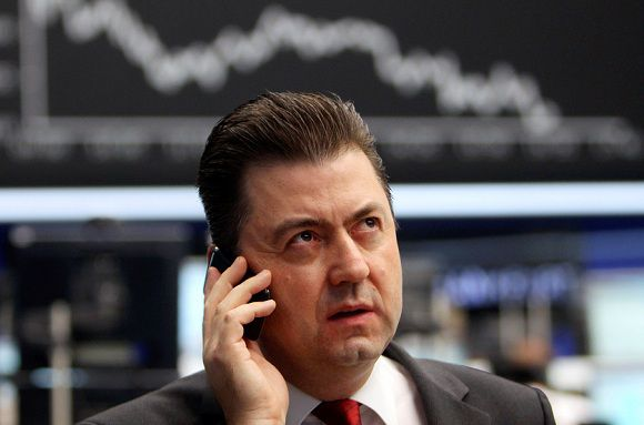 Caption: A trader makes a phone call at the stock market in Frankfurt, Germany, Monday, Dec. 12, 2011, as the German stock index DAX dropped more than two per cent. Enthusiasm for riskier assets such as stocks and the euro faded Monday as investors worried that Europe's new pact aimed at fixing the continent's debt crisis would be insufficient. (AP Photo/Michael Probst)