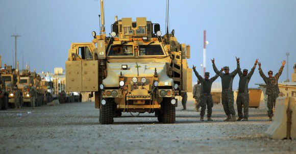 Soldiers from the 3rd Brigade, 1st Cavalry Division gesture in the convoy staging area before departing Camp Adder, now known as Imam Ali Base, near Nasiriyah, Iraq December 17, 2011. The last convoy of U.S. soldiers pulled out of Iraq on Sunday, ending their withdrawal after nearly nine years of war and military intervention that cost almost 4,500 American and tens of thousands of Iraqi lives. Picture taken December 17, 2011. REUTERS/Mario Tama/Pool (IRAQ - Tags: CIVIL UNREST CONFLICT POLITICS)
