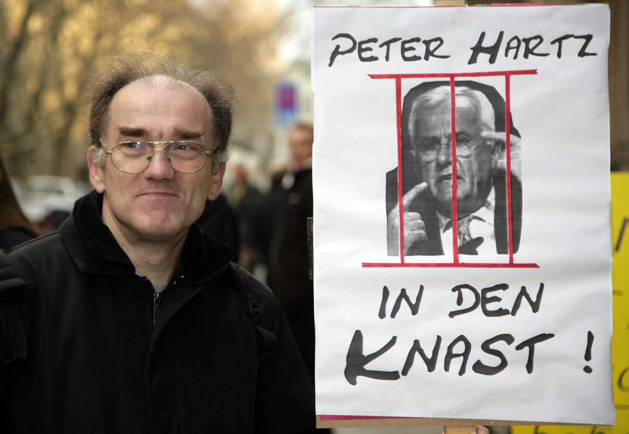 """Demonstranten rond de rechtbank zouden ex-personeelschef Peter Hartz van Volkswagen graag achter de tralies zien. Foto AP Hans-Juergen Zander shows a poster reading """"Peter Hartz to jail"""" prior to the start of the trial against Volkswagen AG's former personnel chief Peter Hartz, on Wednesday, Jan. 17, 2007, in a corruption case that has shone an unsavory light on the cozy relationship between the company's management and labor representatives. The case rests on accusations that key labor officials at the company, including a current member of the German parliament, were showered with illegally financed perks. (AP Photo/Kai-Uwe Knoth)"""