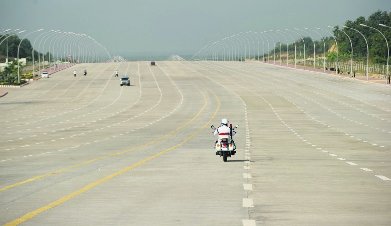A policeman drives down Yazahdani Road on the way to the President's Office prior to a meeting between Myanmar's President Thein Sein and U.S. Secretary of State Hillary Rodham Clinton in Naypyidaw, Myanmar Thursday, Dec. 1, 2011. (AP Photo/Saul Loeb, Pool)
