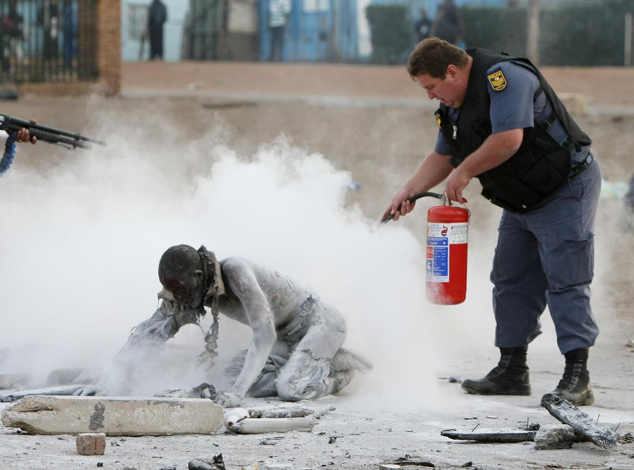 Politie probeert een man te redden die door sloppenwijkbewoners in brand was gestoken. Foto Reuters Policemen try to save a man who was set alight by a mob during clashes believed to be linked to recent anti-foreigner violence in Reiger Park informal settlement east of Johannesburg, May 18, 2008. Hundreds of foreigners living in South Africa took refuge in police stations and churches as week-old violence against them spread further across poor townships, local media reported on Sunday. REUTERS/Stringer (SOUTH AFRICA) TEMPLATE OUT