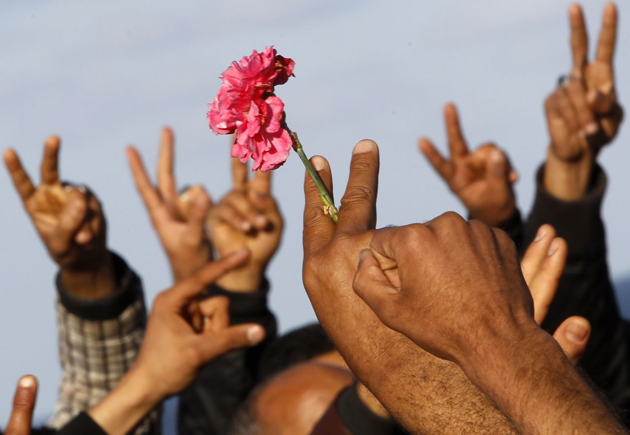 """A Libyan holding a flower joins others during the funeral of people who were killed after air strikes by coalition forces, at the martyrs' cemetery in Tripoli March 20, 2011. Western forces pounded Libya's air defences and patrolled its skies on Sunday, but their day-old intervention hit a serious diplomatic setback as the Arab League chief condemned the """"bombardment of civilians"""". REUTERS/Ahmed Jadallah (LIBYA - Tags: CIVIL UNREST POLITICS)"""