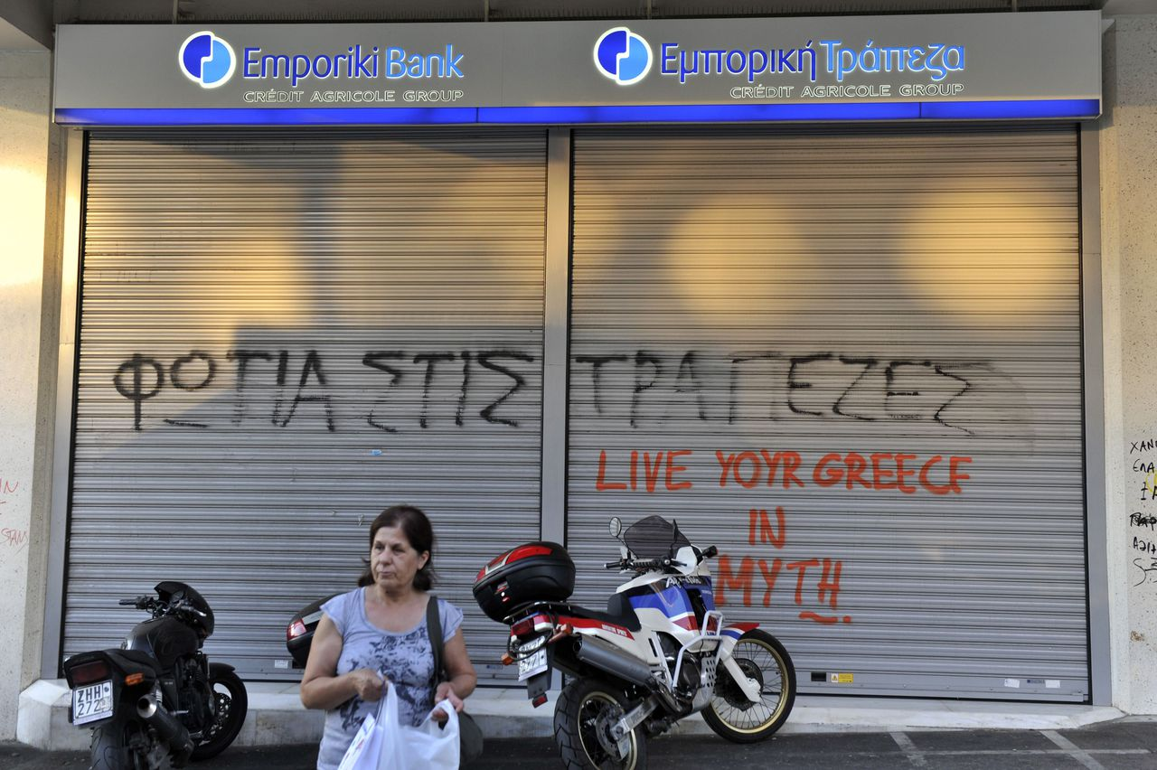 "A woman stands by a bank in Athens, sprayed with slogans reading ""fire to banks"" and ""live your Greece in myth"" changing the slogan of the Greek tourist office on July 12, 2011. Greece rejects any form of partial default on its debt, Finance Minister Evangelos Venizelos said today, denying remarks by the Dutch finance minister on the key eurozone question of private sector involvement. AFP PHOTO/ LOUISA GOULIAMAKI"