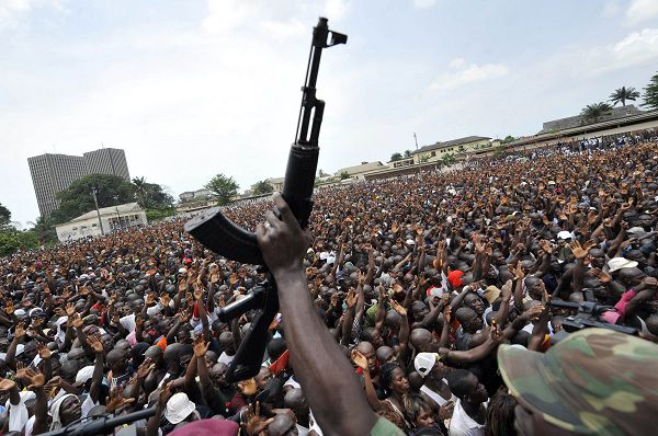 A soldier in the Ivorian Army brandishes his gun in front of thousands of young supporters of (departing) Ivorian president Laurent Gbagbo who gathered to enrol in the Ivorian army, on March 21, 2011 in Abidjan. Fervent backers of Ivory Coast strongman Laurent Gbagbo streamed to enlist in his armed forces today as the UN faced pressure to do more to protect civilians in soaring post-election bloodshed. Gbagbo, who refuses to cede power after disputed November polls, is seeking to boost his army and quash efforts by fighters backing internationally recognised president Alassane Ouattara to seize the economic capital Abidjdan. AFP PHOTO/ SIA KAMBOU