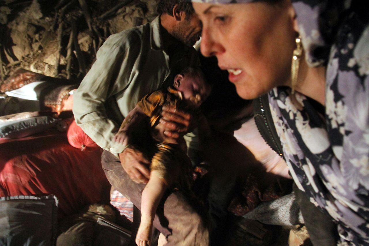 An Iranian man carries the body of a child after finding it in the rubble of a house in Sourmah village, near the town of Varzaqan, after twin earthquakes hit northwestern Iran on August 11, 2012. The two devastating earthquakes in northwest Iran killed around 180 people and injured hundreds as rescue teams were striving to dig survivors out of the rubble. AFP PHOTO/ISNA/FARSHID TIGHEHSAZ