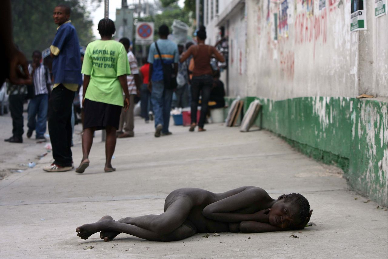 AFP PICTURE OF THE YEAR 2010 A woman, whose medical condition could not be verified, lies on the pavement near the General Hospital where people infected by cholera are being treated, November 16, 2010 in Port-au-Prince. Haiti's cholera death toll passed 1,000 on November 16th, as mounting anger at the health crisis saw tensions spike with UN peacekeepers accused by some of being the source of the outbreak. A Nepalese UN peacekeeping contingent accused of being the source of the cholera outbreak has taken steps to reinforce its protection, the Nepalese army said in Kathmandu. Nepal has about 1,000 troops serving in the UN mission in Haiti. AFP PHOTO / Hector RETAMAL