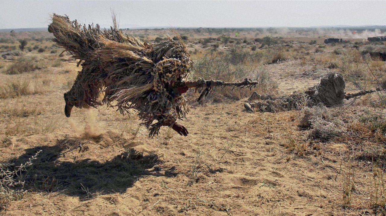 """Indian army soldiers in camouflage take part in exercise """"Sudarshan Shakti"""" at Bugundi in Rajasthan state's Barmer desert near the India Pakistan border, India, Monday, Dec.5, 2011. (AP Photo) INDIA OUT"""