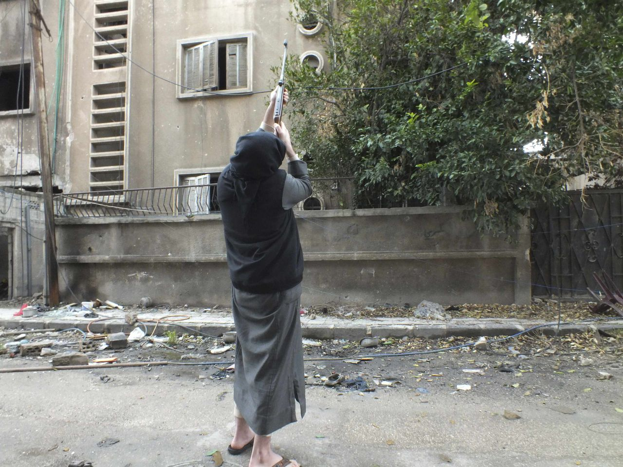 A man uses his rifle to hunt birds for food in the al-Khalidiya neighbourhood of Homs December 5, 2012. REUTERS/Yazan Homsy (SYRIA - Tags: CONFLICT SOCIETY)