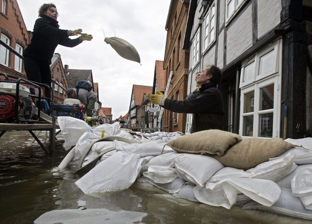 In Hitzacker werpen inwoners dijken op van zandzakken om hun woningen tegen het Elbewater te beschermen. Foto AFP Residents of the northern German town of Hitzacker pile up sandbags to protect their home against the floods of the river Elbe 08 April 2006. The swollen Elbe river rose to record levels in parts of northern Germany, but authorities said the worst of recent flooding would soon be over. AFP PHOTO DDP/ROLAND MAGUNIA GERMANY OUT