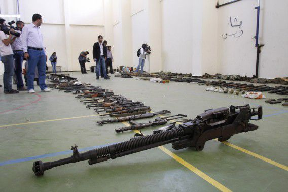 In this photo taken during a government-organised tour for media, Syrian journalists, background, view weapons which according to the Syrian security forces, were found at the town of Rastan, in the central province of Homs, Syria, on Thursday Oct. 13, 2011. Rastan recently witnessed some of the most intense clashes since the uprising began in mid-March. Syrian army took the town earlier this month after a five-day offensive. Syrian troops clashed Thursday with armed men believed to be military defectors in a southern village and a northwestern town, killing at least 13 people in the latest sign that the 7-month-old uprising against President Bashar Assad is becoming increasingly militarized, activists said. (AP Photo/Muzaffar Salman)