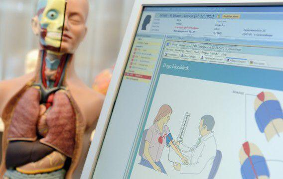 Een anatomisch model naast een computer met daarop een elektronisch patiëntendossier in een huisartsenpraktijk.