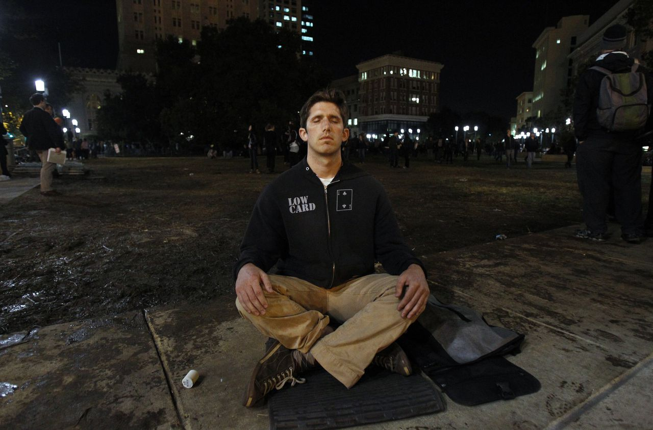 """A man meditates as """"Occupy Wall Street"""" demonstrators rally at Frank Ogawa Plaza outside Oakland City Hall in California October 26, 2011. Atlanta and Oakland joined a growing list of cities losing patience with weeks of protests against economic inequality, evicting and arresting scores of people and leaving one person in Oakland critically injured. REUTERS/Stephen Lam (UNITED STATES - Tags: CIVIL UNREST BUSINESS EMPLOYMENT)"""