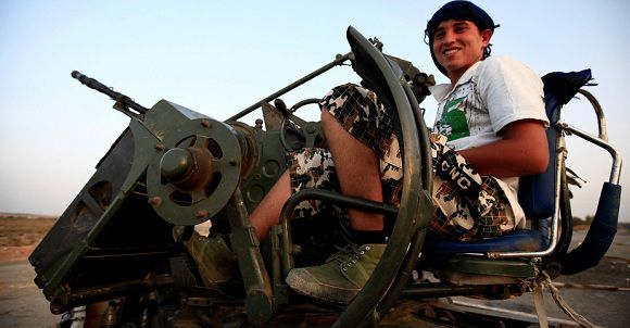 Caption: Ottman Mohamed ,18, an anti-Gaddafi fighter from the Warfallah tribe smiles as he waits outside the town of Bani Walid, currently held by pro-Gaddafi forces, 160 km (100 miles) southeast of Tripoli September 3, 2011. REUTERS/Zohra Bensemra (LIBYAPOLITICS UNREST - Tags: POLITICS CIVIL UNREST MILITARY)
