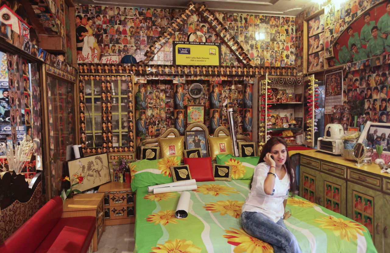 """Ruchi Singh, wife of Vishal Singh, speaks on a phone in their bedroom in Lucknow October 25, 2011. Singh is a fan of the Bollywood actor Shah Rukh Khan and has more than 22,000 pictures of the star in his possession. Singh's house, which he calls """"Shahrukh palace,"""" and even his workplace, are covered with posters featuring the actor. Singh even changed his name to Vishahrukh Khan as a display of his love for the actor. Picture taken on October 25, 2011. REUTERS/Pawan Kumar (INDIA - Tags: SOCIETY)"""
