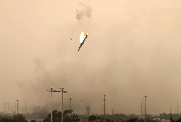 A parachute (L) is ejected from a Libyan jet bomber as it crashes after being hit over Benghazi on March 19, 2011 as Libya's rebel stronghold came under attack, with at least two air strikes and sustained shelling of the city's south sending thick smoke into the sky. AFP PHOTO/PATRICK BAZ