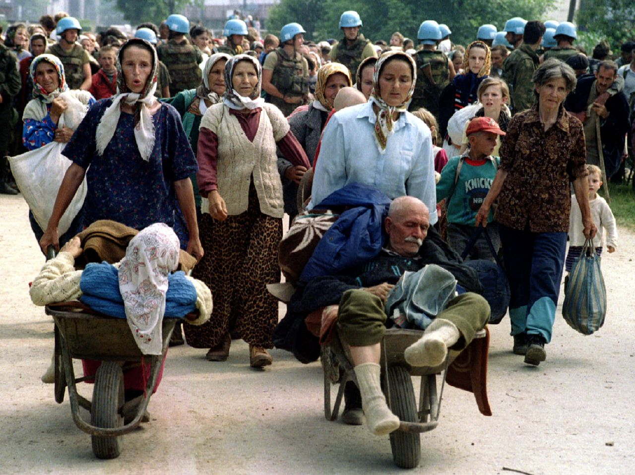 """Group of Bosnian Moslems, refugees from Srebrenica, walk to be transported from eastern Bosnian village of Potocari to Moslem held Kladanj near Olovo July 13. Some 20,000 refugees fled Srebrenica after Bosnian Serbs overran the former """"safe area"""". **YUGOSLAVIA OUT"""