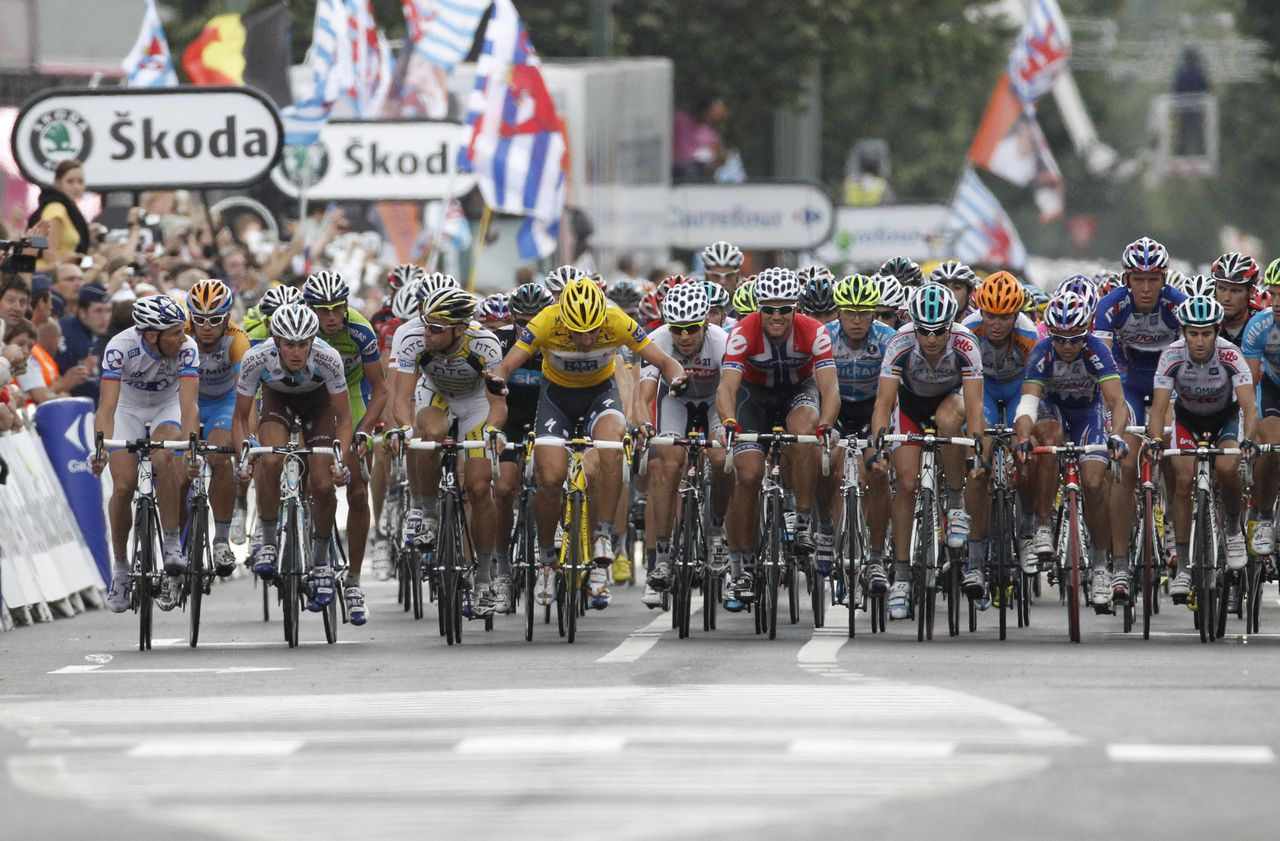 Fabian Cancellara of Switzerland, wearing the overall leader's yellow jersey, center, urges all riders not to engage in a sprint out of protest as the pack crosses the finish during the second stage of the Tour de France cycling race over 201 kilometers (125 miles) with start in Brussels and finish in Spa, Belgium, Monday July 5, 2010. (AP Photo/Laurent Rebours)