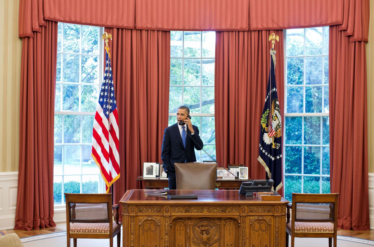 """This official White House photograph shows US President Barack Obama talking on the phone with Solicitor General Donald Verrilli in the Oval Office of the White House June 28, 2012 in Washington, DC, after learning of the Supreme Court's ruling on the """"Patient Protection and Affordable Care Act."""" AFP PHOTO / Official White House Photo / Pete Souza == RESTRICTED TO EDITORIAL USE / MANDATORY CREDIT: """"AFP PHOTO / THE WHITE HOUSE / PETE SOUZA"""" / NO SALES / NO MARKETING / NO ADVERTISING CAMPAIGNS / DISTRIBUTED AS A SERVICE TO CLIENTS == (This official White House photograph is being made available only for publication by news organizations and/or for personal use printing by the subject(s) of the photograph. The photograph may not be manipulated in any way and may not be used in commercial or political materials, advertisements, emails, products, promotions that in any way suggests approval or endorsement of the President, the First Family, or the White House)"""