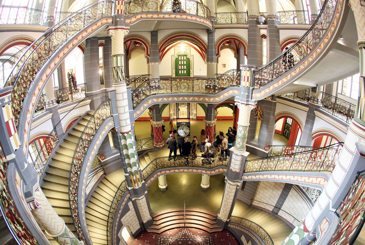 TOPSHOTS Visitors stand in the staircase of the restored former Prussian justice palace, that serves now as county court in Halle an der Saale, eastern Germany, on April 22, 2013. The 110 years old building housing 20 courtrooms, 110 offices and further 100 rooms re-opened after two years of restoration. AFP PHOTO / JAN WOITAS / GERMANY OUT
