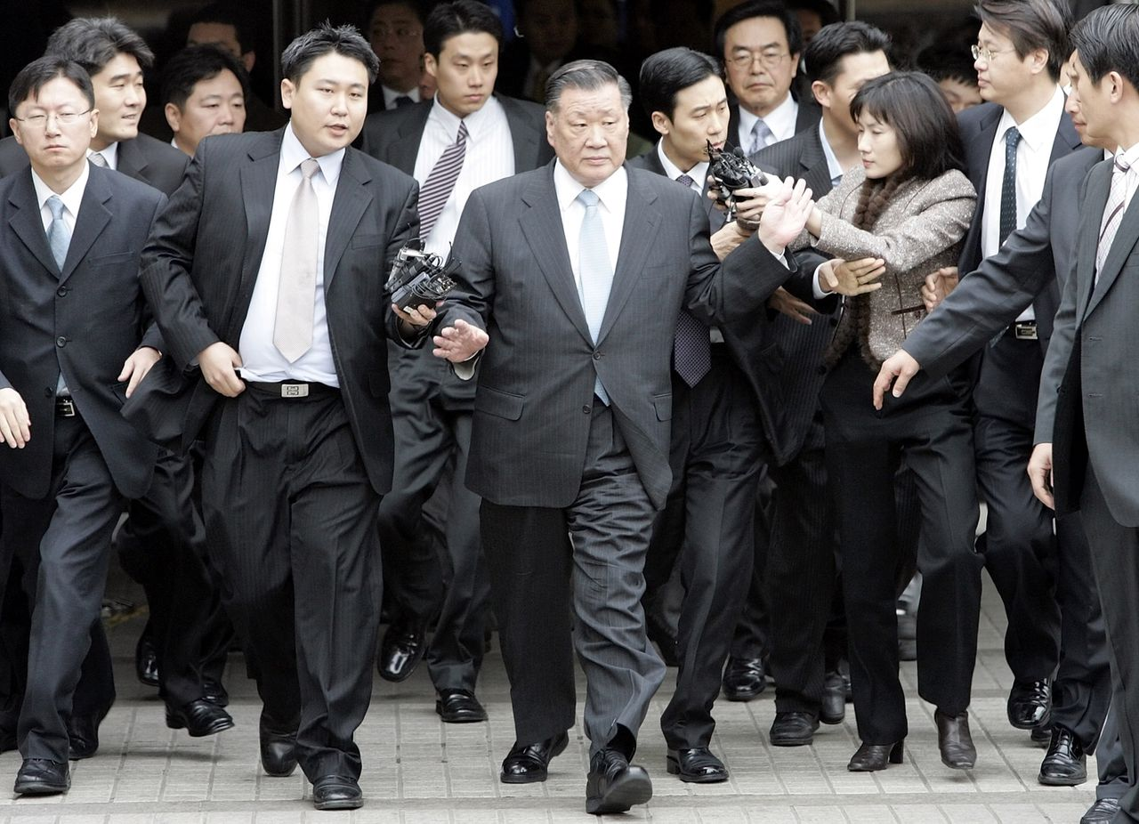 Bestuursvoorzitter van Hyundai, Chung Mong-koo (midden), wimpelt journalisten af na afloop van zijn rechtszaak in Seoul. Foto AP Hyundai Motor Co. Chairman Chung Mong-koo, center, breaks free from the reporters after finished his trial at the Seoul Central District Court in Seoul, Monday, Feb. 5, 2007. Hyundai Motor Co. Chairman Chung Mong-koo was convicted Monday of embezzlement and other charges and sentenced to three years in prison over a slush fund scandal that has weighed on South Korea's largest automaker. (AP Photo/ Lee Jin-man)