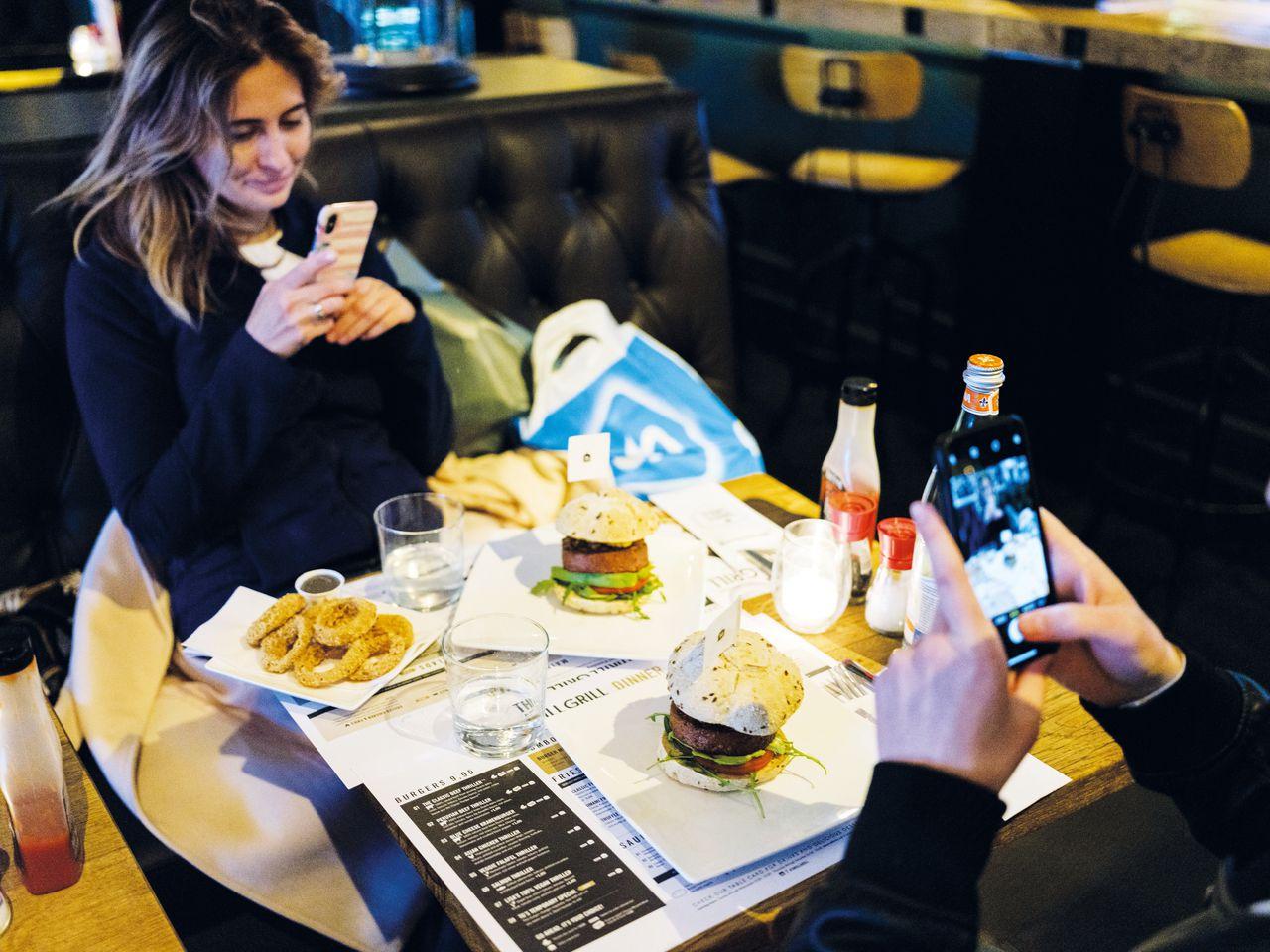 Viktoria en Andri Kozak uit Kiev fotograferen de Beyond Burger op hun bord in een Amsterdams burgerrestaurant.