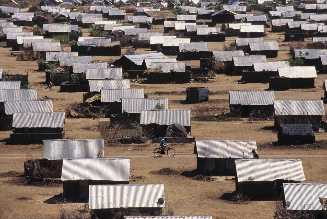 """A Third and Final Home-[Documentary Summary: The twelve-thousand Somali Bantus living in the Kakuma refugee camp have the perversely unique distinction of being a thrice-displaced people. Situated in the northeastern corner of Kenya, Kakuma has been the Bantus' latest home after being forcibly displaced several times: first by the eastern African slave trade several hundreds of years (to enslavement in Somalia) and second by the disintegration of the state of Somalia in 1991 (to refugee camps in Kenya). Barred from returning to their ancestral homeland, the Bantus are on the move again, this time to the United States, in what will remain their permanent new home. I traveled to Kakuma in the Spring of 2004 to document life in the refugee camp as well as the Somali Bantus long-awaited journey to their new home.] -Untitled Photograph-As the punishing sun begins to heat up the morning, a lone Somali Bantu biker cuts through the """"streets"""" of Kakuma, past houses made of mud-brick and topped with tin roofs."""