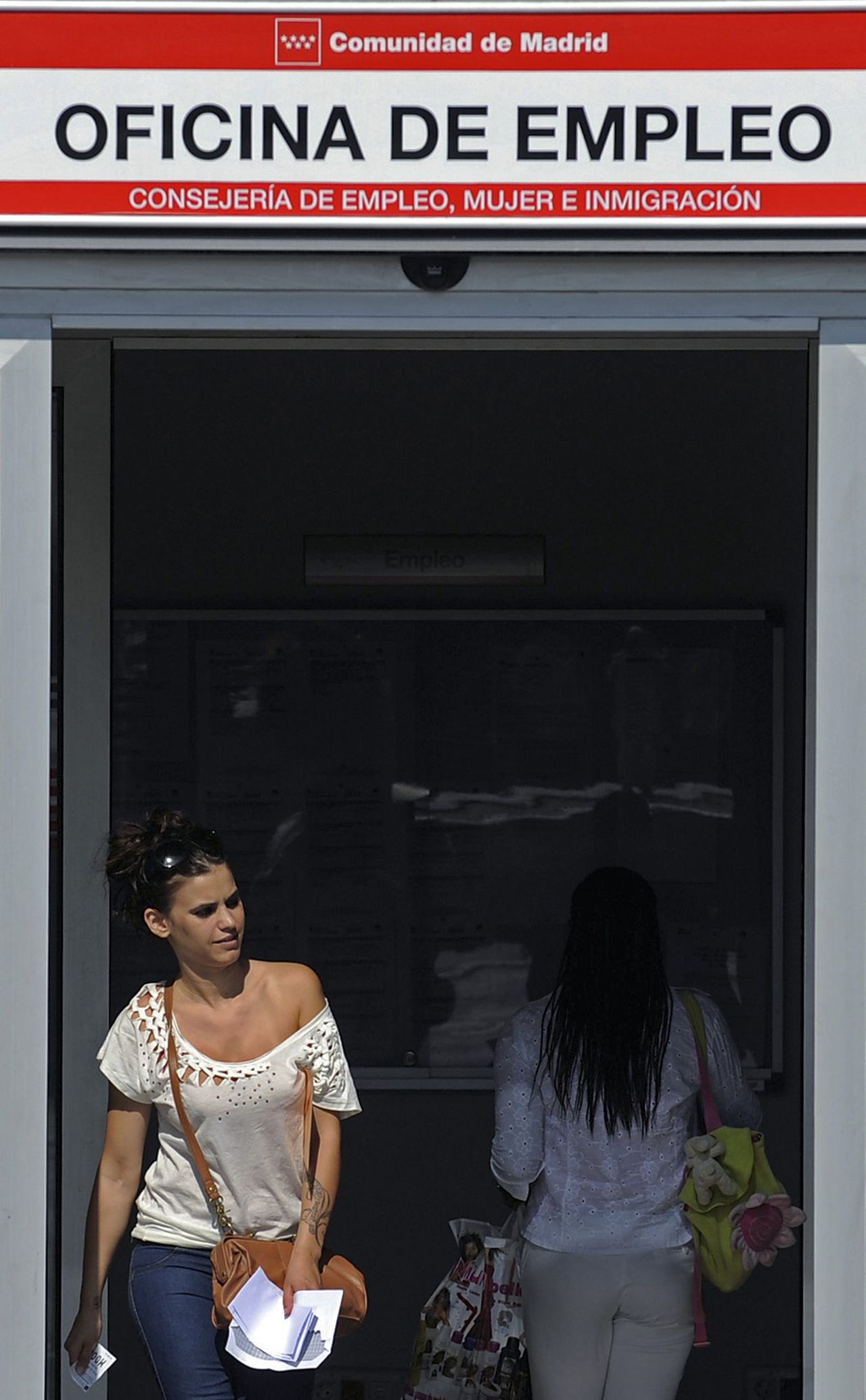 A woman leaves an employment agency in Madrid, Spain, on Thursday, June 30, 2011. Bank of Spain Governor Miguel Angel Fernandez Ordonez called for a deeper overhaul of labor laws to tackle the country's 21 percent unemployment rate, the highest in Europe, which he said is an obstacle to the economic recovery and sustainable public finances. Photographer: Denis Doyle/Bloomberg