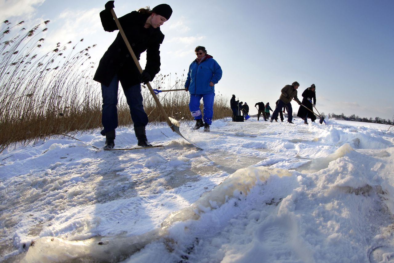 Volunteers shovel away snow from the frozen Holkenmeer or Holken lake in Gallemadammen, Netherlands, Tuesday Feb. 7, 2012. Volunteers poured onto frozen rivers and lakes in the northern Netherlands on Tuesday to shovel away snow that is one of the major hurdles in the way of a grueling speedskating race called Elfstedentocht, or 11 Cities Tour being held for the first time in 15 years. (AP Photo/Vincent Jannink)