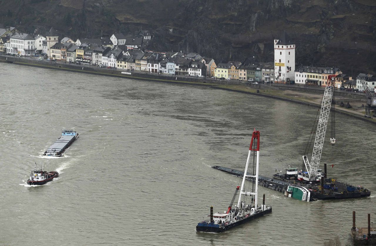 Tanker Waldhof geladen met 2.400 ton zwavelzuur wordt gelift waarna de lading wordt overgepompt. Foto Reuters Rescue ships work next to a tanker ship, which capsized in the middle of the Rhine (Rhein) river, Europe's most important shipping way for commodities, near Sankt Goarshausen January 23, 2011. The river has been partially reopened to shipping after being blocked by the capsized tanker loaded with sulphuric acid, the German inland navigation authority said on Thursday. REUTERS/Alex Domanski (GERMANY)