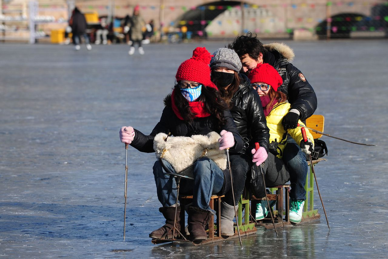 People skate across a frozen lake at Shichahai in central Beiijng on January 5, 2011. Despite a relatively mild winter for Beijingers in the north, where traditional outdoor winter activities remain popular as ever, frigid weather in south and central China has forced the emergency evacuation of around 58,000 people and caused 1.35 billion yuan (204 million US dollars) in economic losses, the government said. AFP PHOTO/Frederic J. BROWN