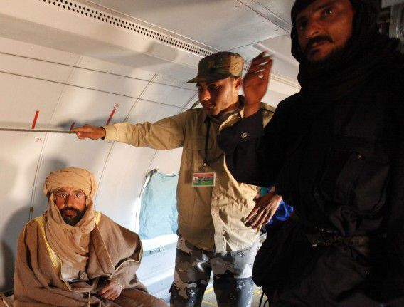 Saif al-Islam Gaddafi is pictured sitting in a plane in Zintan November 19, 2011. Saif al-Islam Gaddafi told Reuters on Saturday that he was feeling fine after being captured by some of the fighters who overthrew his father and he said injuries to his right hand were suffered during a NATO air strike a month ago. REUTERS/Ismail Zitouny (LIBYA - Tags: POLITICS CIVIL UNREST)