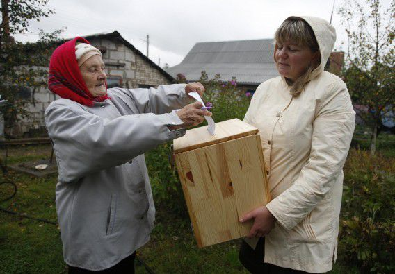 A woman casts her vote into a portable ballot box during the parliamentary elections near her house in the village of Slobodschina, about 30 km (19 miles) northeast of Minsk, September 23, 2012. Belarus voted on Sunday in a parliamentary election which was likely to reinforce hardline President Alexander Lukashenko's grip on the small former-Soviet country despite a boycott call from the dispirited opposition. REUTERS/Vladimir Nikolsky (BELARUS - Tags: POLITICS ELECTIONS)