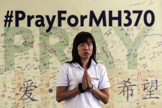 Een boeddhistische vrouw bidt voor het vermiste vliegtuig van Malaysia Airlines