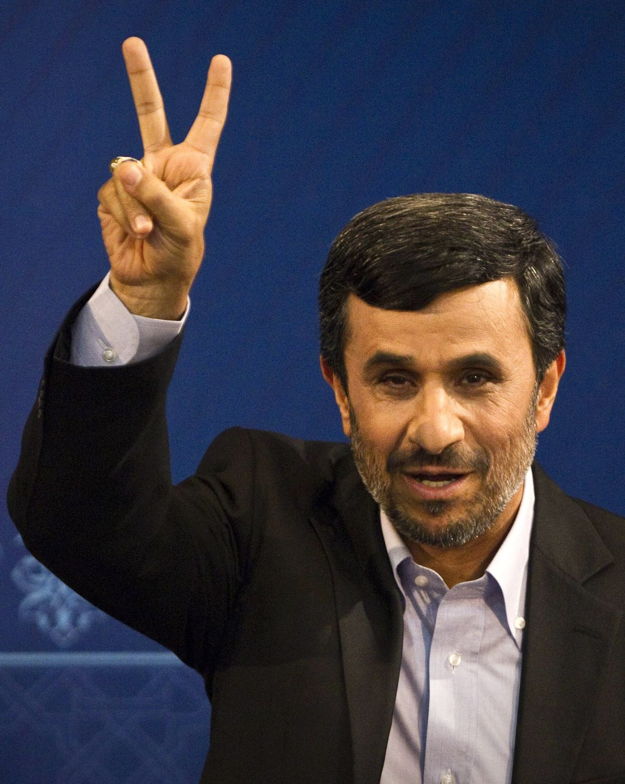 """(FILES) A picture taken on June 7, 2011 shows Iranian President Mahmoud Ahmadinejad flashing the victory sign during a press conference in Tehran. Ahmadinejad condemned the """"killings and massacre"""" in Syria in an interview with CNN on October 22, 2011, in Iran's strongest criticism yet of its key ally's deadly seven-month-old crackdown on dissent. AFP PHOTO/BEHROUZ MEHRI"""