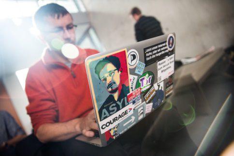 Een journalist heeft op zijn laptop een sticker met het gezicht van Edward Snowden.