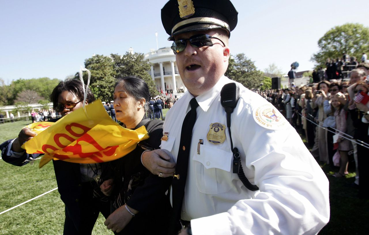Een demonstrant wordt weggevoerd terwijl... A protester is arrested after shouting and waving a banner during the welcoming ceremony for Chinese President Hu Jintao on the South Lawn of the White House April 20, 2006. U.S. President George W.Bush and Hu will discuss trade, currency, Iran and Taiwan during their meeting today, but analysts say the White House meeting is unlikely to yield any significant agreements. REUTERS/Kevin Lamarque