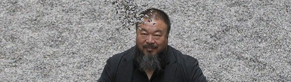 "Chinese artist Ai Weiwei throws porcelain sunflower seeds into the air as he poses with his installation ""Sunflower Seeds"", in the Turbine Hall at the Tate Modern gallery, in London in this October 11, 2010 file photo. Ai, 53, who designed Beijing's iconic Bird's Nest Olympic Stadium, was due to fly to Hong Kong for business on April 3, 2011 morning but was detained at immigration on his way out of the capital city, according to news reports. The studio of the outspoken government critic was also raided by the police, according to Ai's assistant. REUTERS/Stefan Wermuth/Files (BRITAIN - Tags: SOCIETY POLITICS)"