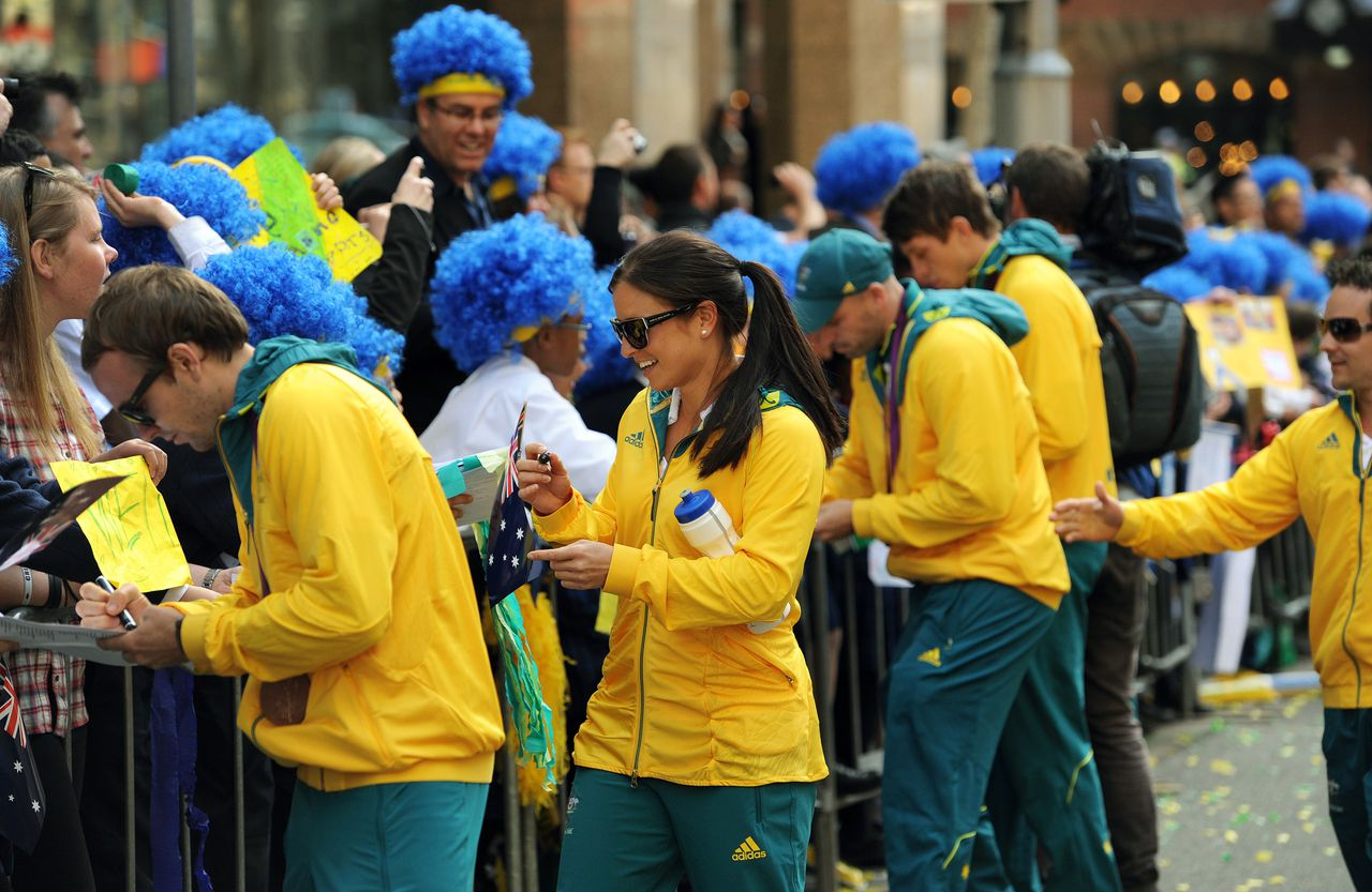 Australian Olympians sign autographs for spectators as the Australian Olympic team was officially welcomed home from the 2012 London Olympic Games with a colourful street parade through Sydney on August 20, 2012. Australia finished 10th on the medal table, a slump from its performance in Beijing where it claimed 6th position, leading to a rush of criticism that the team underperformed. AFP PHOTO / Greg WOOD