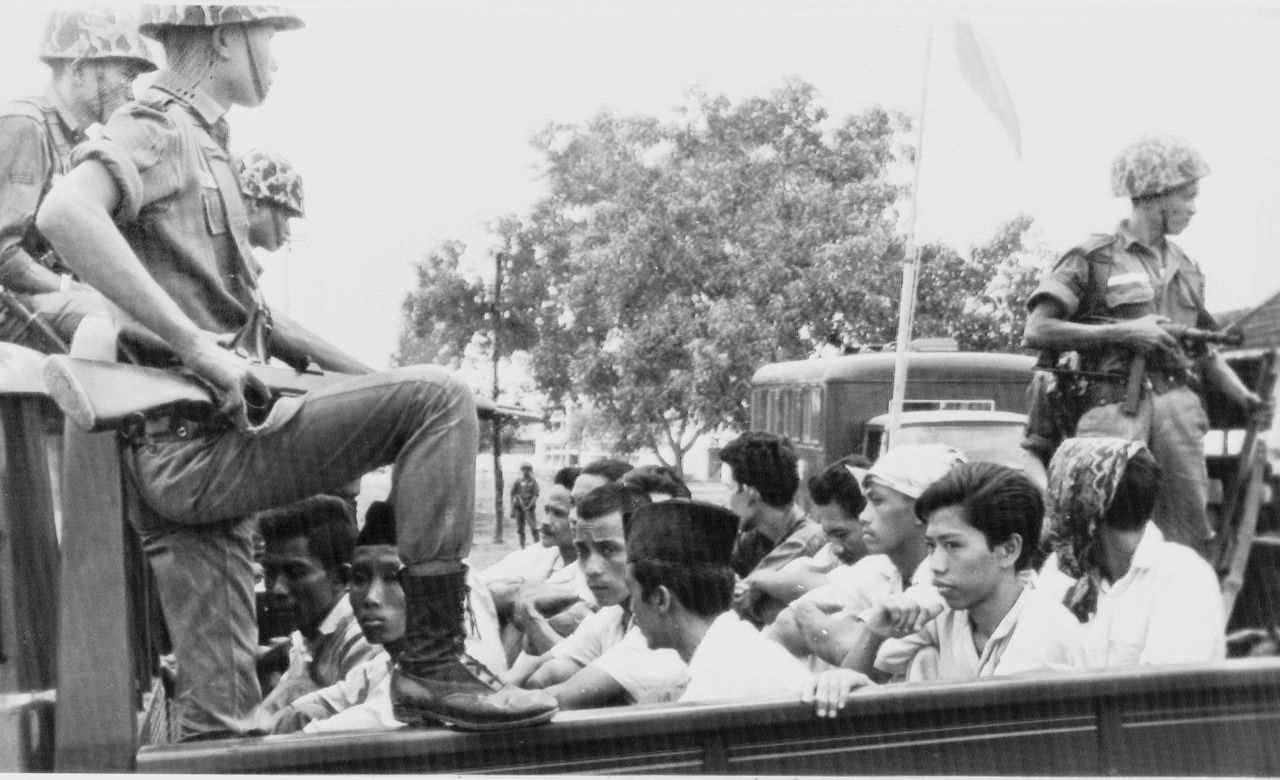 ** FILE ** Members of the Youth Wing of the Indonesian Communist Party (Pemuda Rakjat) are guarded by soldiers as they are taken by open truck to prison in Jakarta, in this Oct. 30, 1965, file photo. Historians estimate that between 300,000 and 800,000 Indonesians were killed in Gen. Suharto's bloody rise to power from 1965 to 1968, the worst mass slaughter in Southeast Asia's modern history after the Khmer Rouge killing fields in Cambodia. A frenzy of anti-communist violence stained rivers with blood and littered the countryside with the bodies of teachers, farmers and others. (AP Photo/File)