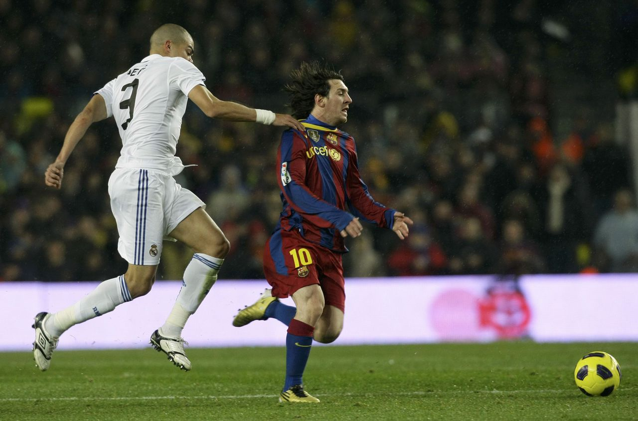 Barcelona's Lionel Messi (R) is grabbed by Real Madrid's Pepe during their Spanish first division soccer match at Nou Camp stadium in Barcelona, November 29, 2010. REUTERS/Albert Gea (SPAIN - Tags: SPORT SOCCER)