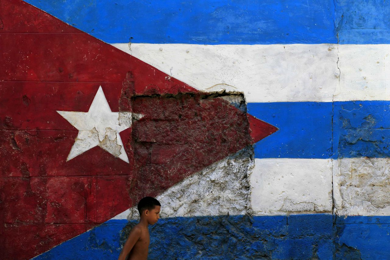 A child walks under a Cuban flag in Havana October 21, 2012. Former Cuban leader Fidel Castro is alive and well, according to Elias Jaua, a former Venezuelan vice president who says he met with Castro over the weekend. Squelching rumours that Castro was at death's door, Jaua, a key aide to Venezuelan President Hugo Chavez, on Sunday showed reporters pictures of the Saturday meeting and said Castro, 86, was in good health and lucid. REUTERS/Enrique De La Osa (CUBA - Tags: POLITICS)