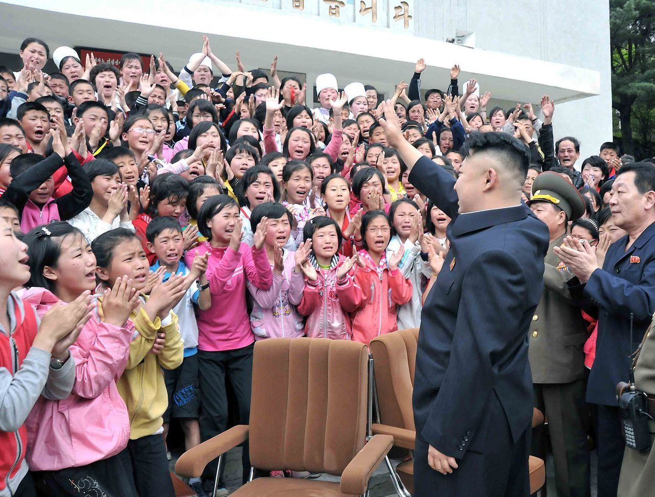 """This photo taken on May 19, 2013 and released by North Korea's official Korean Central News Agency (KCNA) on May 20, 2013 shows North Korean leader Kim Jong-Un (front R) waving to the children during a visit to the Pyongyang Myohyangsan Children's Camp, situated at the foot of Mt. Myohyang (Myohyang-san) in North Phyongan Province. Meanwhile, South Korea on May 20 predicted further missile tests by North Korea which fired four short-range missiles into the Sea of Japan at the weekend, drawing criticism from Seoul and UN chief Ban Ki-moon. AFP PHOTO / KCNA via KNS THIS PICTURE WAS MADE AVAILABLE BY A THIRD PARTY. AFP CAN NOT INDEPENDENTLY VERIFY THE AUTHENTICITY, LOCATION, DATE, AND CONTENT OF THIS IMAGE. THIS PHOTO IS DISTRIBUTED EXACTLY AS RECEIVED BY AFP. -----EDITORS NOTE----- RESTRICTED TO EDITORIAL USE - MANDATORY CREDIT """"AFP PHOTO / KCNA via KNS"""" - NO MARKETING NO ADVERTISING CAMPAIGNS - DISTRIBUTED AS A SERVICE TO CLIENTS"""