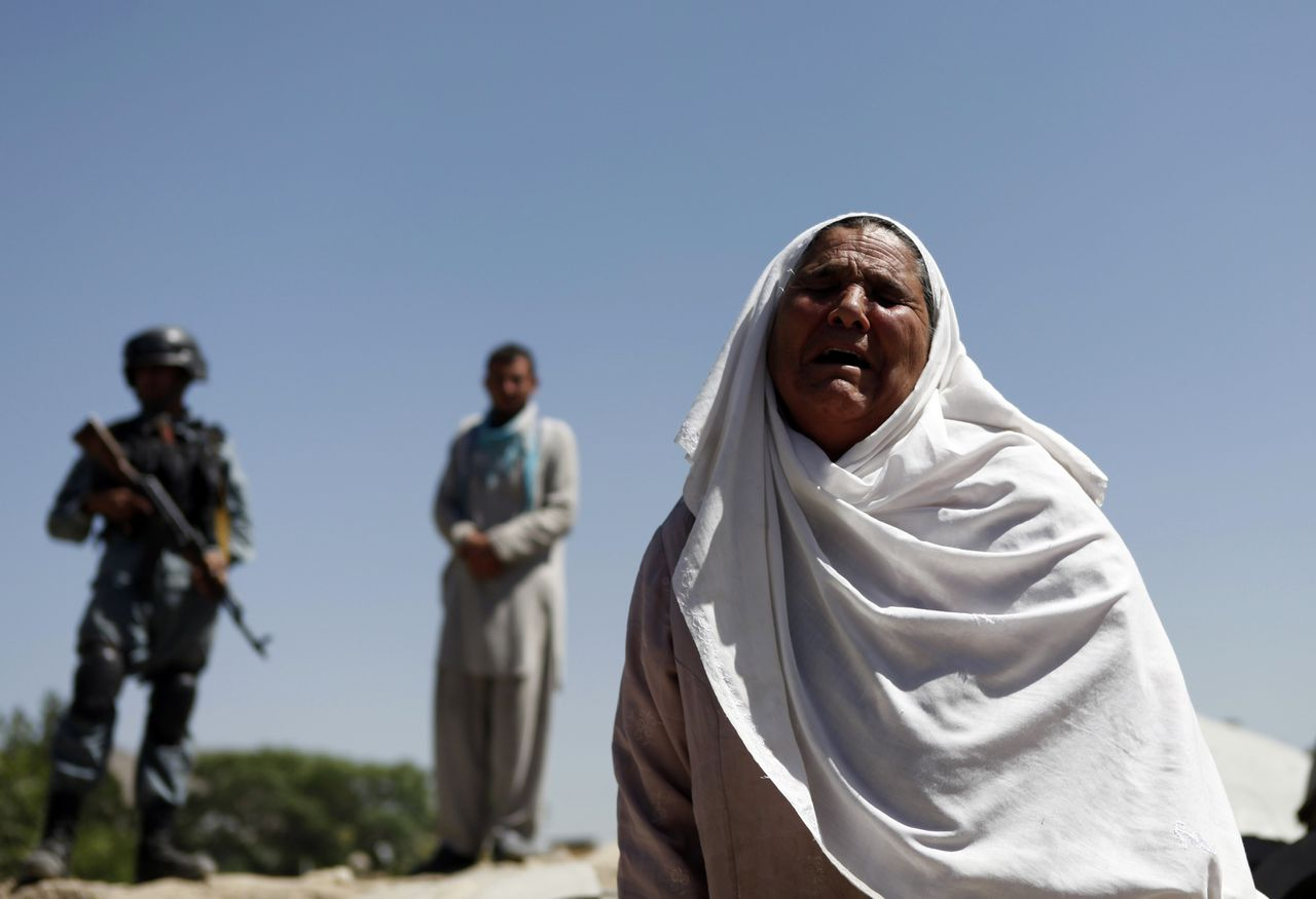 A woman cries at the site of an explosion in Kabul June 18, 2013. A bomb targeted a senior Shia Muslim cleric in the west of Kabul on Tuesday, police said, shortly before the international military coalition marked its final handover of security to national forces. REUTERS/Mohammad Ismail (AFGHANISTAN - Tags: CIVIL UNREST POLITICS)